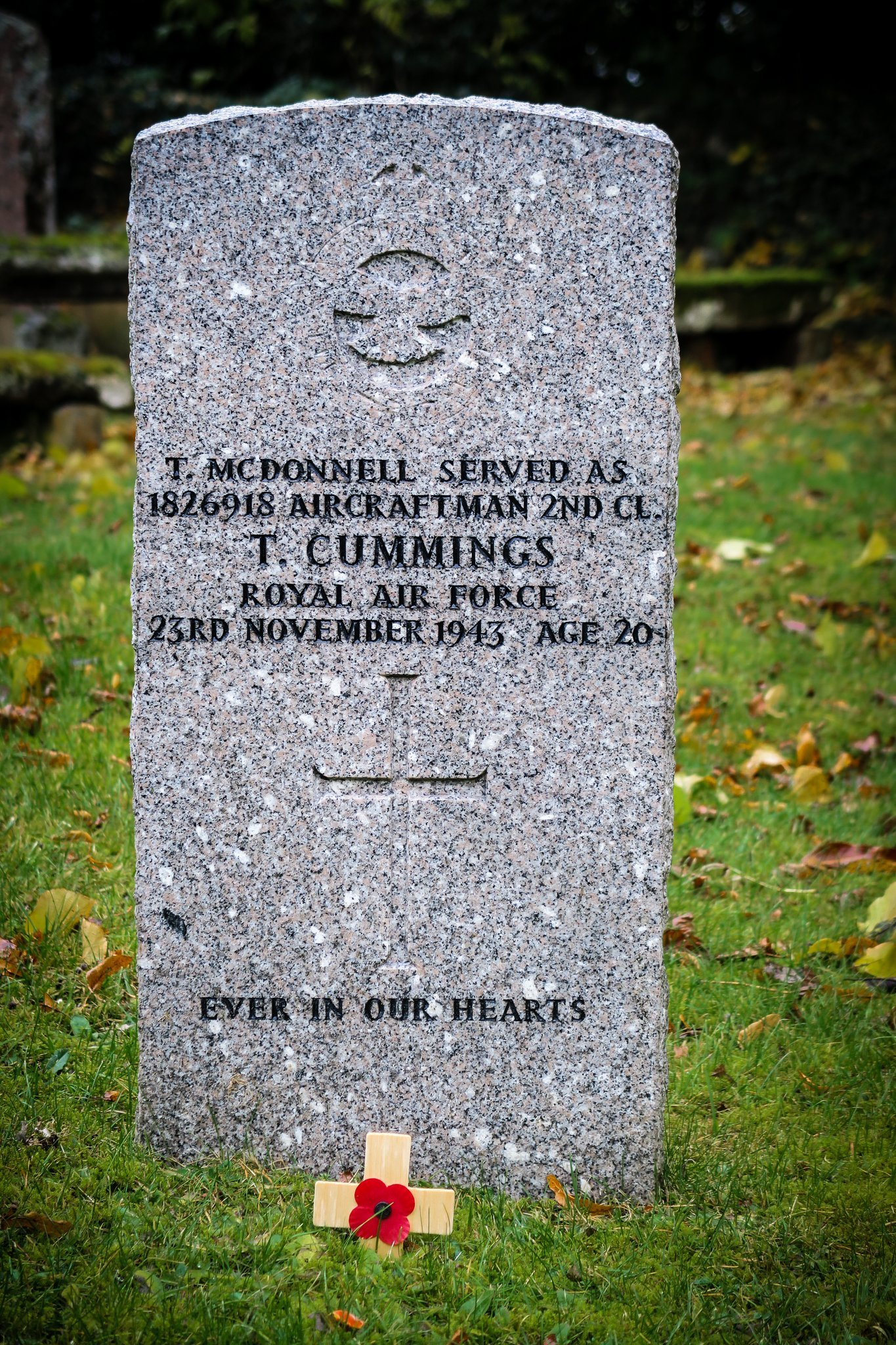 Gravestone of a young airman killed in the 2nd world war, with a poppy attached to a small cross in the foreground