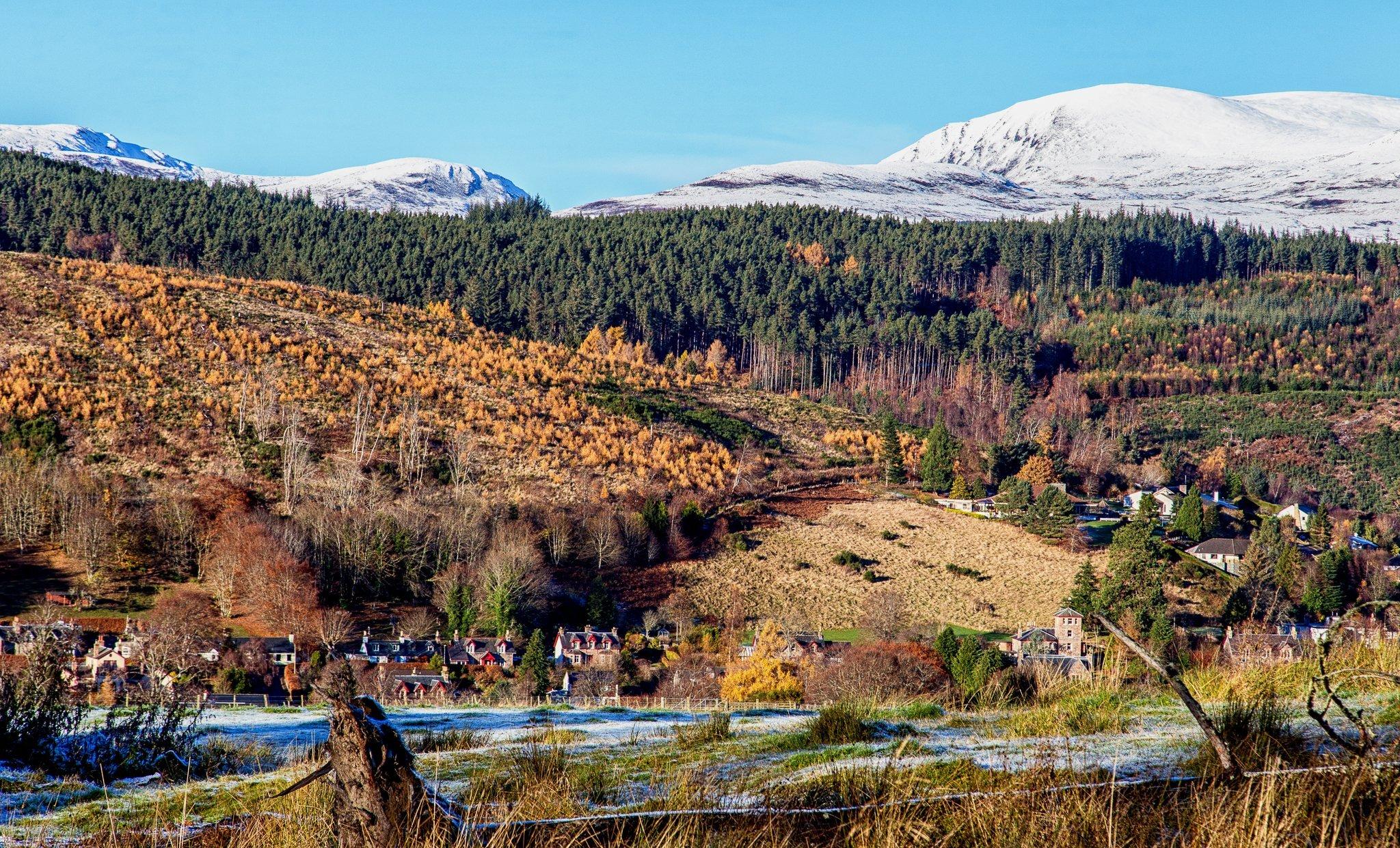 View across a frosty field to Strathpeffer and the snow-capped hills beyond