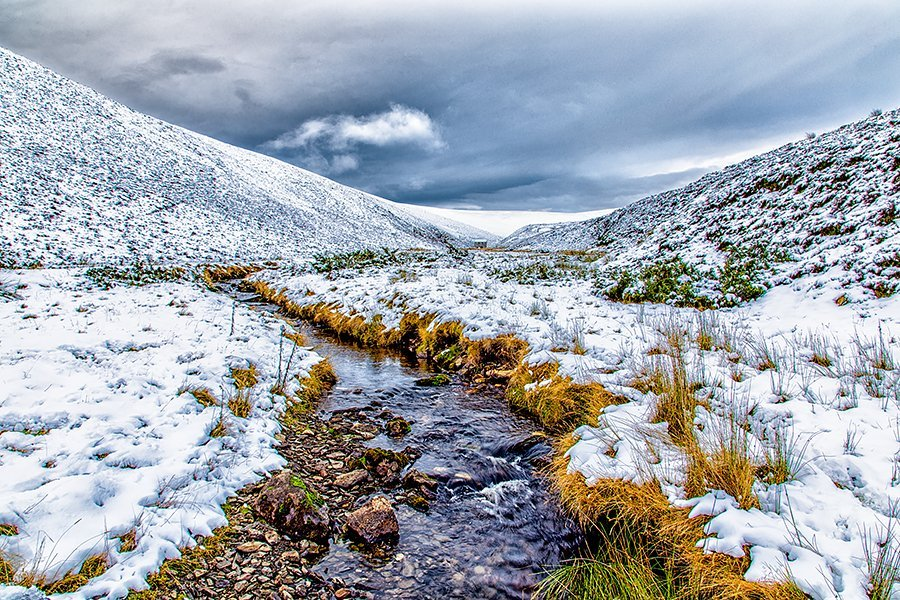 A small river running through the snow covered valley